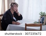 Small photo of Senior woman looking at dead husband's picture