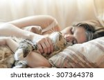 Stock photo girl sleeping in bed with her cat 307364378