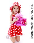 Small photo of Adorable little girl in a short summer dress with polka dots and matching hat, knelt down and holding a gift box-Isolated on white background