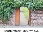 Small photo of An entrance gate in a wall into a park. Behind the open door is a way.