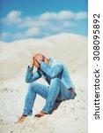 bronzed man sitting on the sand ... | Shutterstock . vector #308095892
