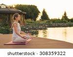 woman meditating near lake on... | Shutterstock . vector #308359322