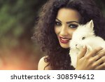 Stock photo portrait of beautiful young brunette happy woman with curly hair and bright makeup holding cute 308594612