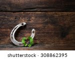 Stock photo st patricks day four leaved clover and a horseshoe on wooden board 308862395