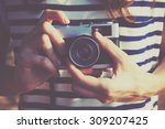 girl holding retro camera and... | Shutterstock . vector #309207425