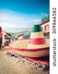 "Small photo of Mexican hat ""sombrero"" on a ""serape"" in a mexican town"
