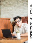 young asian man drinking coffee ... | Shutterstock . vector #310196846