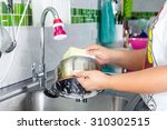women hand washing pans in sink | Shutterstock . vector #310302515