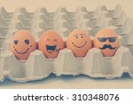 four brown eggs  with faces... | Shutterstock . vector #310348076