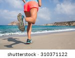 young woman running on a sandy... | Shutterstock . vector #310371122