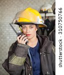 Small photo of Portrait of confident firewoman using walkie talkie at fire station