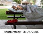 homeless man sleeping on a... | Shutterstock . vector #310977806