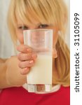 Small photo of beautiful blond woman drinking a glass of milk and having a milksop