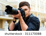 Photography is my passion. Confident young man photographing something while standing outdoors - stock photo