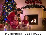 family on christmas eve at... | Shutterstock . vector #311449232