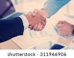 Small photo of Confident business handshake. Close-up view of a handshake while two successful businessman shaking hands at the table against each in the business office in formal wear and work at a laptop.