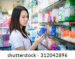 young female pharmacist picking ... | Shutterstock . vector #312042896