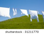 Stock photo white clothes hanging on the line against blue sky and a green hill 31211770