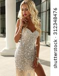 Small photo of fashion outdoor photo of elegant beautiful woman with blond hair in luxurious sequins dress and silver accessories,posing in summer park