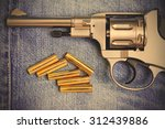 Small photo of revolver with cartridges on old blue jeans background, close up. instagram image filter retro style