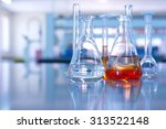 Small photo of conical flask glassware with orange solution in chemical science laboratory in school or university technology background