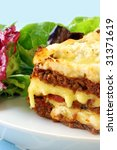 Beef lasagne with melting mozzarella and ricotta cheeses, with a salad. - stock photo