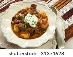 Traditional beef goulash, topped with sour cream.  Delicious homely food. - stock photo