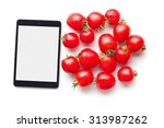 computer tablet and tomatoes on white background - stock photo