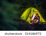 Overnight Forest Camping. Middle Age Caucasian Hiker with His Digital Camera and the Illuminated at Night Green Tent. Nighttime Mountains Hike and the Camping. - stock photo