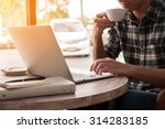 Stock photo businessman using laptop with tablet and pen on wooden table in coffee shop with a cup of coffee 314283185