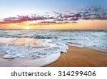 Stock photo colorful ocean beach sunrise with deep blue sky and sun rays 314299406