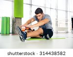 Stock photo portrait of a fitness man doing stretching exercises at gym 314438582