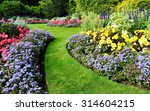Scenic View of Colourful Flowerbeds and a Winding Grass Lawn Pathway in an Attractive English Formal Garden - stock photo
