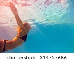 Young Woman Swimming Undewater...