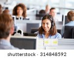 Small photo of Young woman working in call centre, surrounded by colleagues