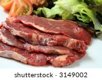 Fresh angus filet on a dish with vegetables for salad - stock photo
