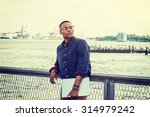 Stock photo african american businessman traveling on east river in new york a black college student standing 314979242