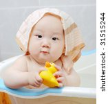 Asian baby boy holding  a yellow plastic duck in bath - stock photo