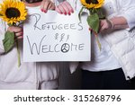 female helpers welcome refugees | Shutterstock . vector #315268796