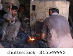 Small photo of KARACHI, PAKISTAN - SEP 11: Blacksmiths are busy in preparing butcher knives use to cut animals on the occasion of Eid-ul-Azha coming ahead, at Bohra Pir area on September 11, 2015 in Karachi.