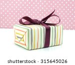 Gift Box With Purple Bow On...