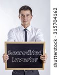 Small photo of Accredited Investor - Young businessman holding chalkboard with text
