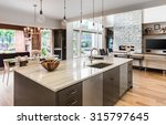 Stock photo kitchen with island sink cabinets and hardwood floors in new luxury home with view of living 315797645