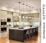 Stock photo beautiful kitchen interior in new luxury home with island cabinets pendant lights stainless 315797972