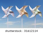 Three toy windmills cut from 100, 50 and 20 euro banknotes over blue sky - stock photo