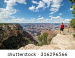 Man standing on rock overlooking the Grand Canyon National Park on the South Rim whilst on outdoor summer vacation holiday in the US
