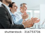 Small photo of Cheerful smiling business people clapping hands during a seminar, success and achievement concept