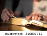 man reading the bible in dim... | Shutterstock . vector #316801712