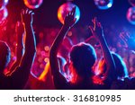 Stock photo group of young people with raised arms dancing in night club 316810985