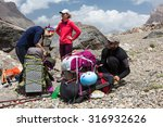 Hikers Packing Backpacks Group...